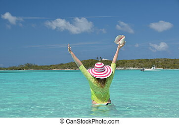 Girl with a seashell in the turqouise water of Atlantic....