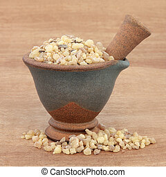 Frankincense in a mortar with pestle over papyrus background...