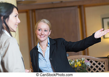 Smiling receptionist helping a hotel guest - Beautiful...