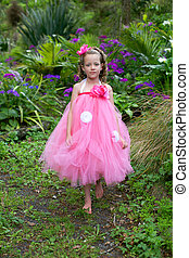 Little ballerina playing in a garden