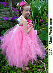 Little ballerina playing in a garden.