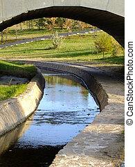 An artificial brook under a bridge