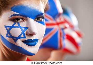 Several people with face art. Israel and Great Britain flags...