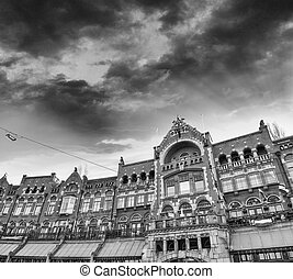 Amsterdam, The Netherlands. Beautiful classic city architecture with country flags and dramatic sky.