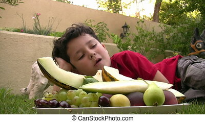 Little boy eating fruit