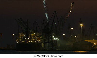 Unloading cargo ship at night 1 - Night view of a harbour in...