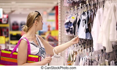 Mother shopping for childrens clothes - Attractive young...
