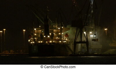 Unloading cargo ship at night 2 - Night view of a harbour in...