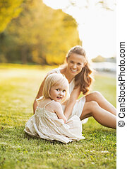 Happy mother and baby sitting on meadow in park