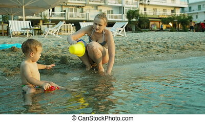 Little boy and his mother playing on the beach in the...