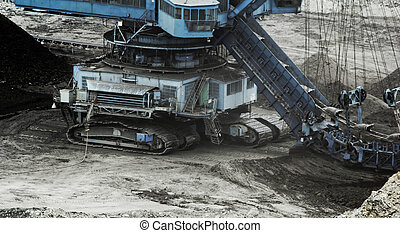 Coal mining in an open pit with huge industrial machine
