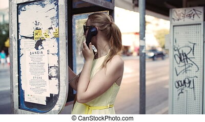 Woman chatting on a public telephone - Attractive woman in...