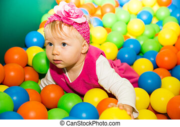 Happy child girl in colored ball on playground The concept...