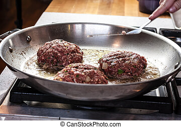 Stir Cooking School - Raw hamburgers cooking in hot...
