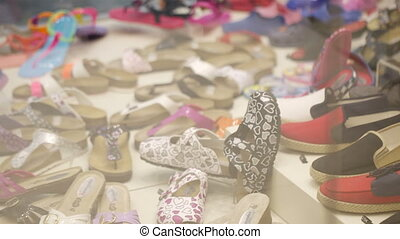 Young girl passing by a shoe shop - Panning shot of a young...