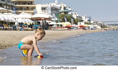 Little boy at a beach resort crouching down in the shallow...