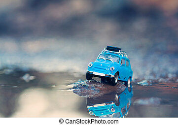 Miniature travelling car with luggage on top. Macro...