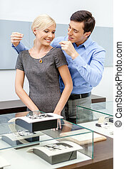 Male puts necklace on his girlfriend at jewelers shop...