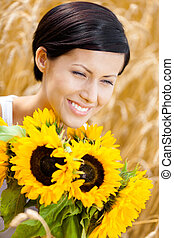 Close up of girl with sunflowers in the field - Close up of...