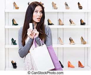 Girl hands credit card in footwear shop - Girl holds credit...