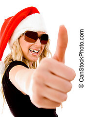 portrait of smiling female with christmas hat showing thumb...