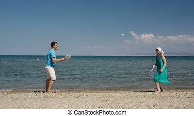 Couple playing bat and ball at the beach