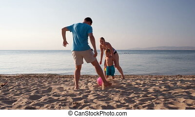 Young family playing football on the beach