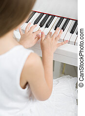 Back view of little child in white dress playing piano -...