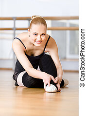 Bending ballerina stretches herself on the wooden floor -...
