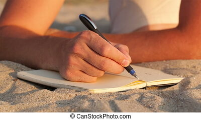Man writing in his diary at the beach while lying on the...