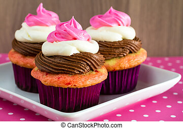 Neapolitan Cupcakes - Close up of 3 neapolitan frosted...