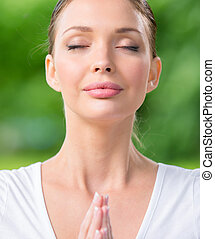 Close up of woman with closed eyes prayer gesturing. Concept...
