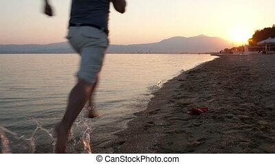 Man running along a beach at sunset