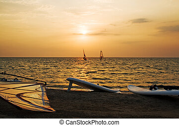 Silhouette of a two windsurfer on a gulf on a sunset