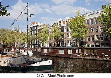 Amsterdam Canal in Netherlands - Boats and houseboats on a...