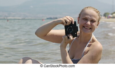 Smiling woman taking a photo at the seaside with her vintage camera