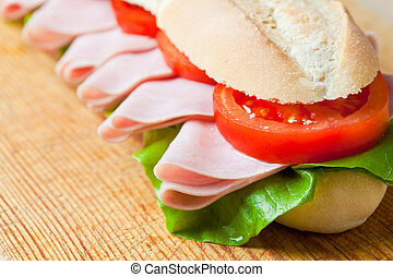 A large ham and tomato baguette