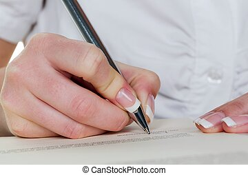hand with fountain pen writes under contract - a woman signs...