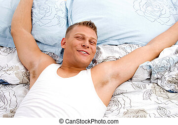 man stretching his arms in bed