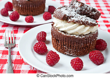 Delicious chocolate and cream muffins on a plate with...