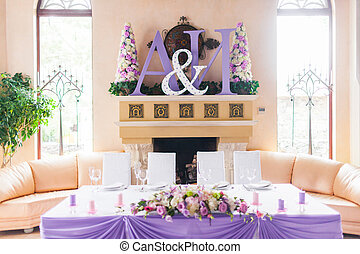 Bride and groom's table decorated with flowers - Interior of...