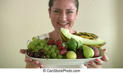 Woman holding plate with fruit - Woman showing lots of...