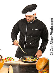Chef garnish vegeatbels on plate - Chef man in black uniform...