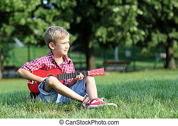boy sitting on grass and play guitar