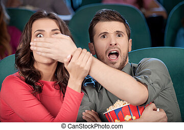 Don?t look at this! Shocked young couple watching movie at the cinema while men covering his girlfriend?s eyes with hands