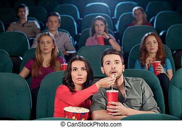 Great movie! Young couple feeding each other while watching movie at the cinema