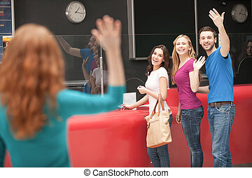 Friends meeting at the cinema Cheerful young people greeting...