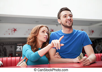 Loving couple at the restaurant. Young loving couple buying...