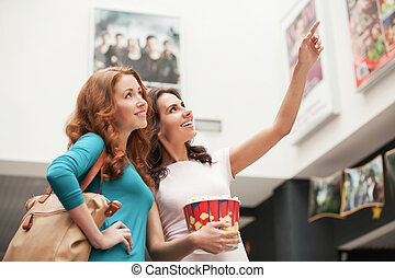Friends choosing movie at the cinema Beautiful young female...