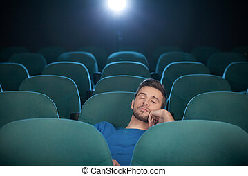 Sleeping at the cinema. Young men sleeping at the cinema and holding his hand on chin
